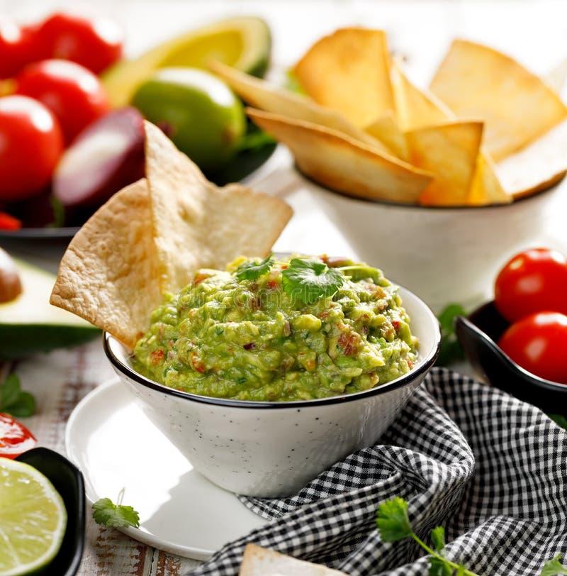 Гуакамоле традиционное мексиканское погружение сделанное из авокадоа, лука, томатов, кориандра, перцев чилей, известки и соли с a стоковые изображения