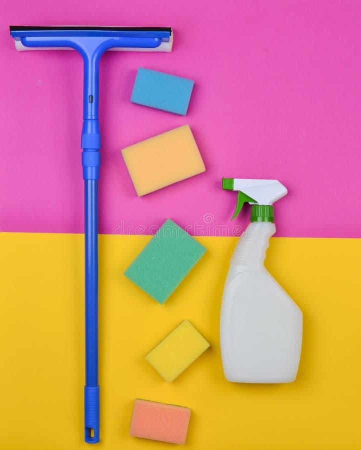 Губки, mop окна, cleanser спринклера на розовой желтой предпосылке Объекты для домашней чистоты Продукты для чистки стоковые фотографии rf