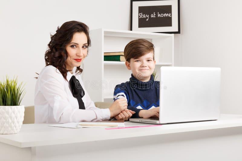 Гувернер и мальчик делая домашнюю работу в белом классе Печатая домашняя работа на ноутбуке стоковые изображения rf