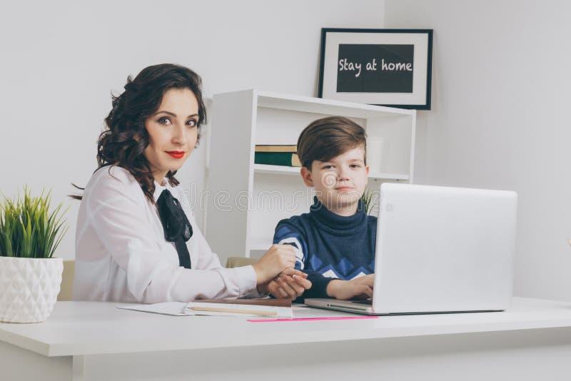 Гувернер и мальчик делая домашнюю работу в белом классе Печатая домашняя работа на ноутбуке стоковые изображения