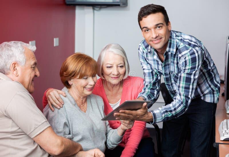 Гувернер направляя старших студентов для использования таблетки цифров в классе стоковые изображения