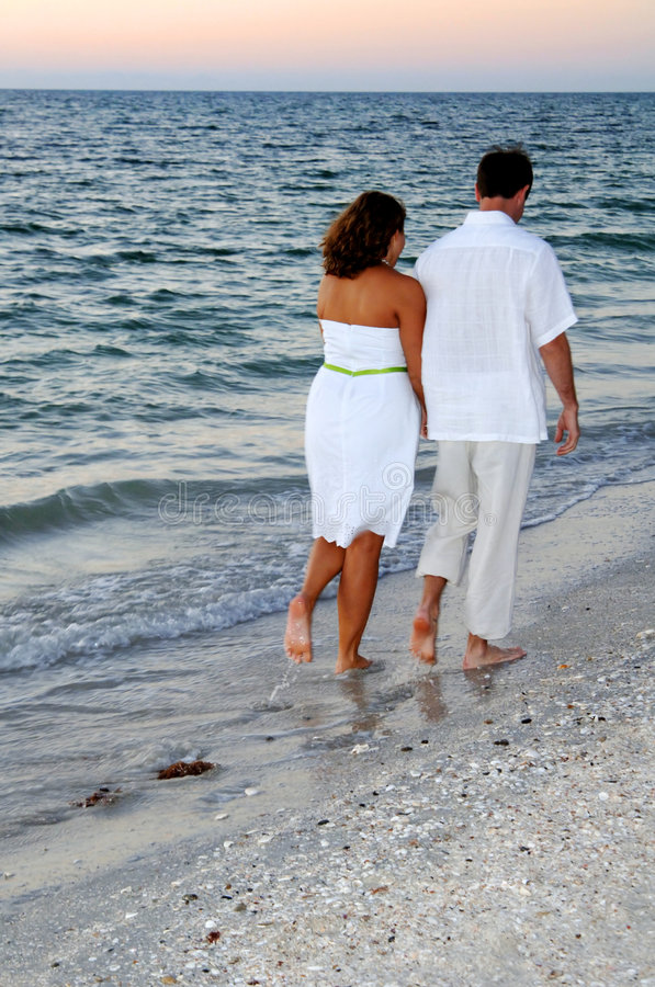 гулять захода солнца пар пляжа стоковая фотография