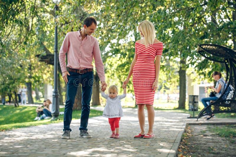 гулять парка семьи мама и папа идя рука об руку с младенцем стоковые изображения rf