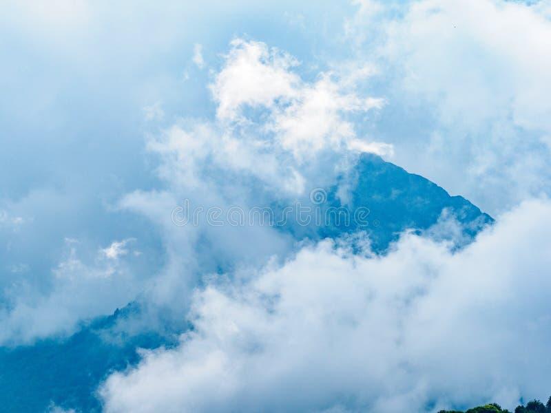 Густой туман в горах на пасмурный день Высокая гора с зелеными наклонами спрятанными в облаках и тумане стоковые изображения