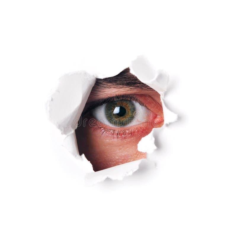 Глаз шпионки наблюдая через отверстие стоковые фотографии rf