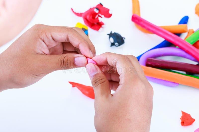 Глина моделирования прессформы ребенка, на белой предпосылке Усильте стоковая фотография
