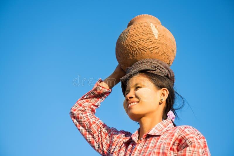 Глиняный горшок нося молодого азиатского традиционного фермера на голове стоковая фотография