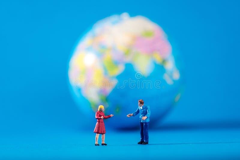 Глобус и миниатюрные люди стоковые фотографии rf