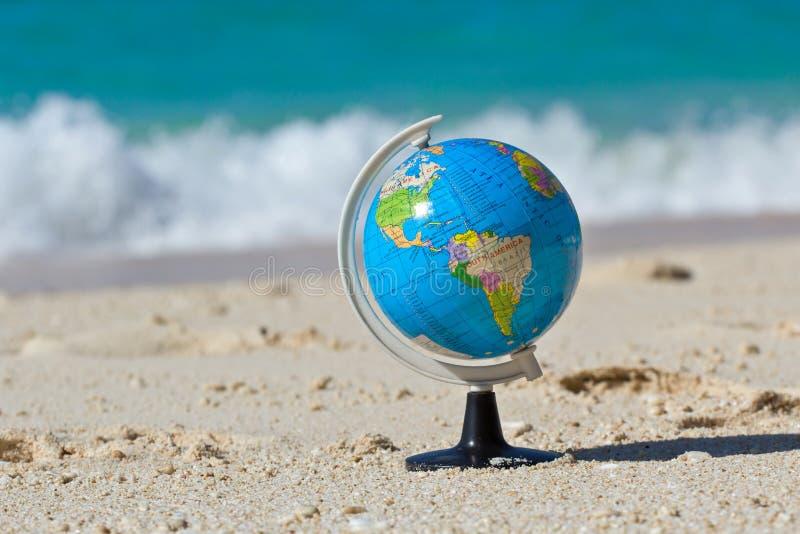 Глобус на карибском пляже стоковые изображения