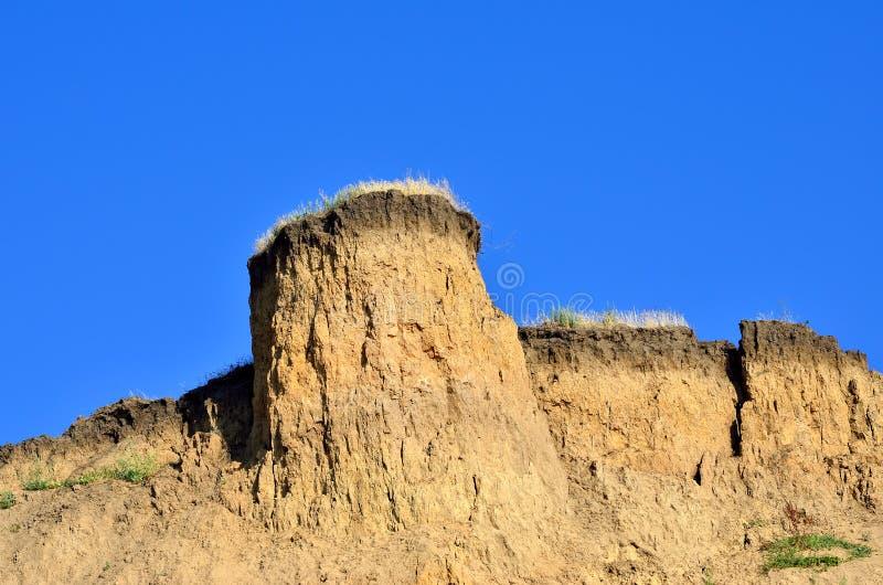 Глубокая песочная скала на предпосылке голубого неба стоковые изображения rf