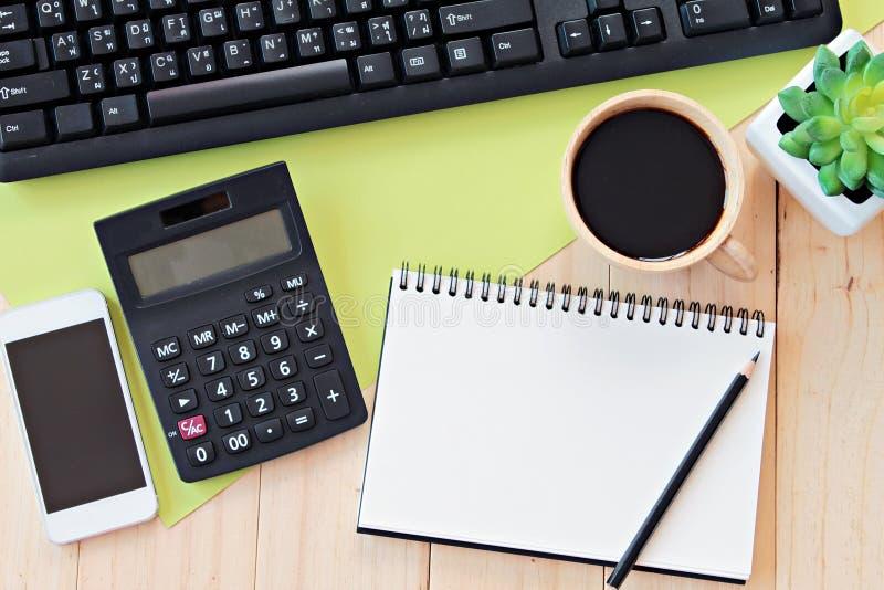 Глумитесь вверх места для работы стола таблицы офиса с пустой тетрадью, умным телефоном, калькулятором, клавиатурой компьютера и  стоковые изображения rf
