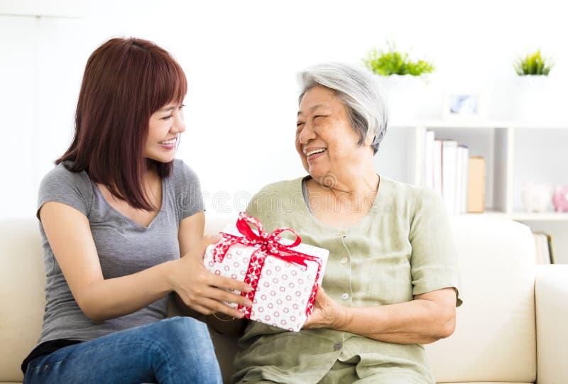 Давать молодой женщины присутствующий к бабушке стоковые фото
