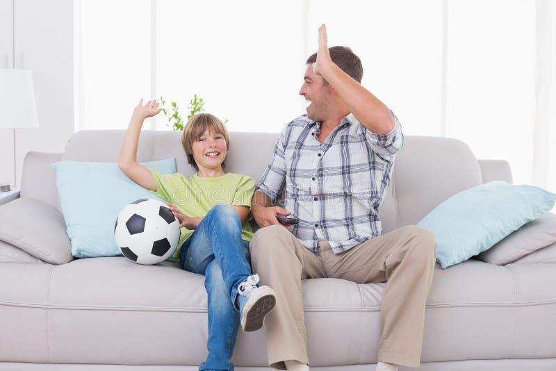 Давать отца и сына высоко--5 пока наблюдающ футбольный матч стоковые изображения rf