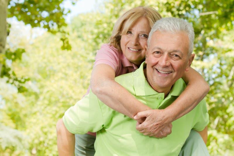 давать счастливый старший piggyback человека стоковая фотография rf