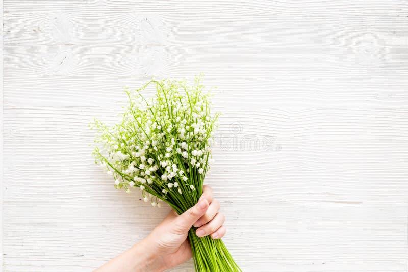 Дайте букет чувствительных цветков ландыша Вручите пук владением цветков на белом экземпляре взгляд сверху предпосылки стоковое изображение