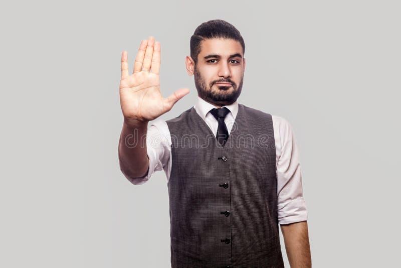 Дайте мне 5 или стоп! Портрет красивого бородатого человека брюнета в белом положении рубашки и жилета, смотря камеру и стоковое фото rf