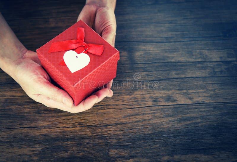 Дайте человека любов держа небольшую красную присутствующую коробку в руках с сердцем для концепции дня Святого Валентина любов стоковая фотография