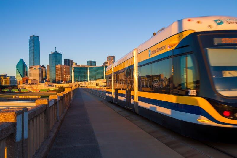ДАЛЛАС, ТЕХАС - 10-ое декабря 2017 - Moving трамвай на виадуке улицы Хьюстона с городом Далласа в предпосылке Dal стоковые изображения rf