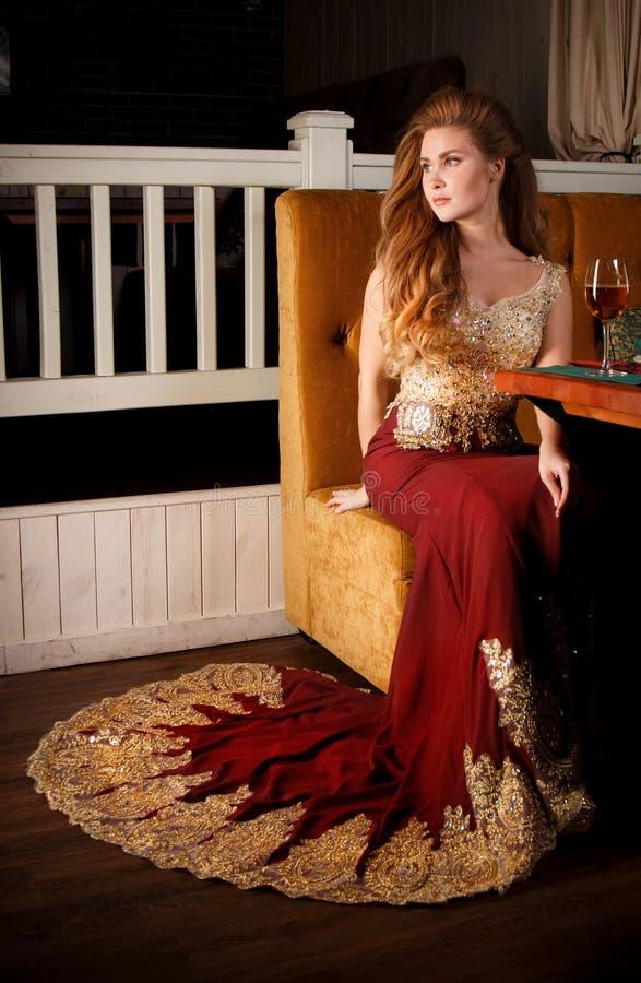Дама в красном платье в ресторане стоковая фотография