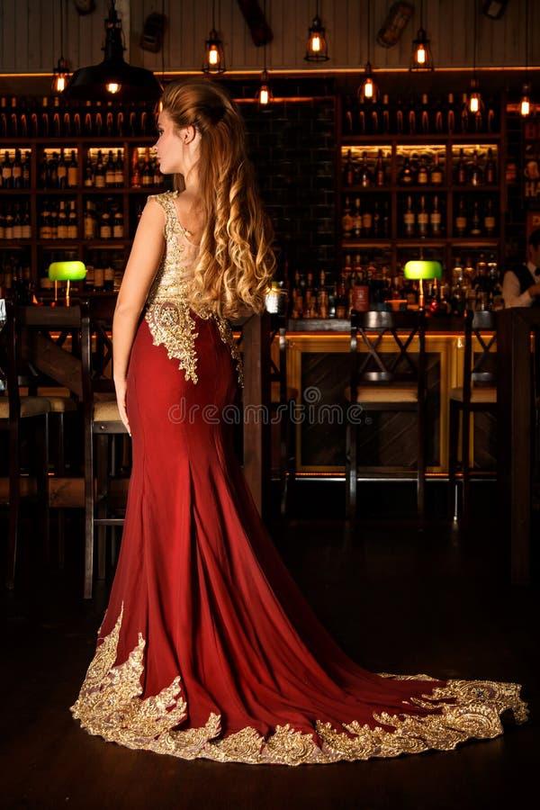 Дама в красном платье в ресторане стоковая фотография rf