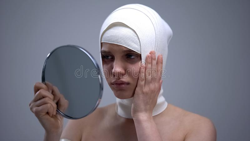 Дама в эластичном headwrap смотря в зеркале, чувствуя боли после пластической хирургии стоковые изображения