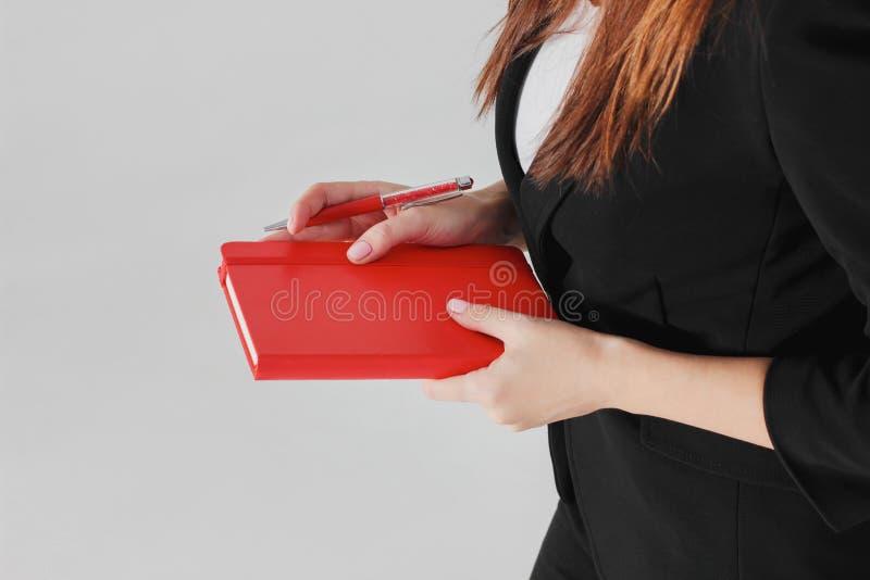 Дама дела женщины в черном костюме с красным плановиком дневника в руках стоковое изображение rf