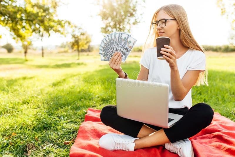 Дама дела при стекла, держа деньги, и выпивая кофе, стоковое изображение