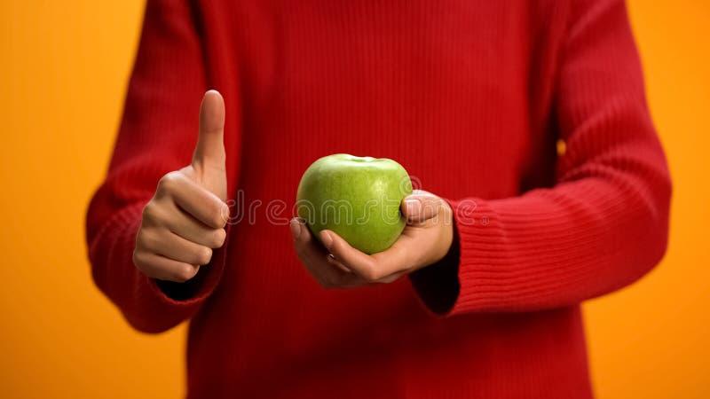 Дама держа зеленую руку яблока показывая большие пальцы руки вверх, закуска плода, здоровое питание стоковая фотография rf