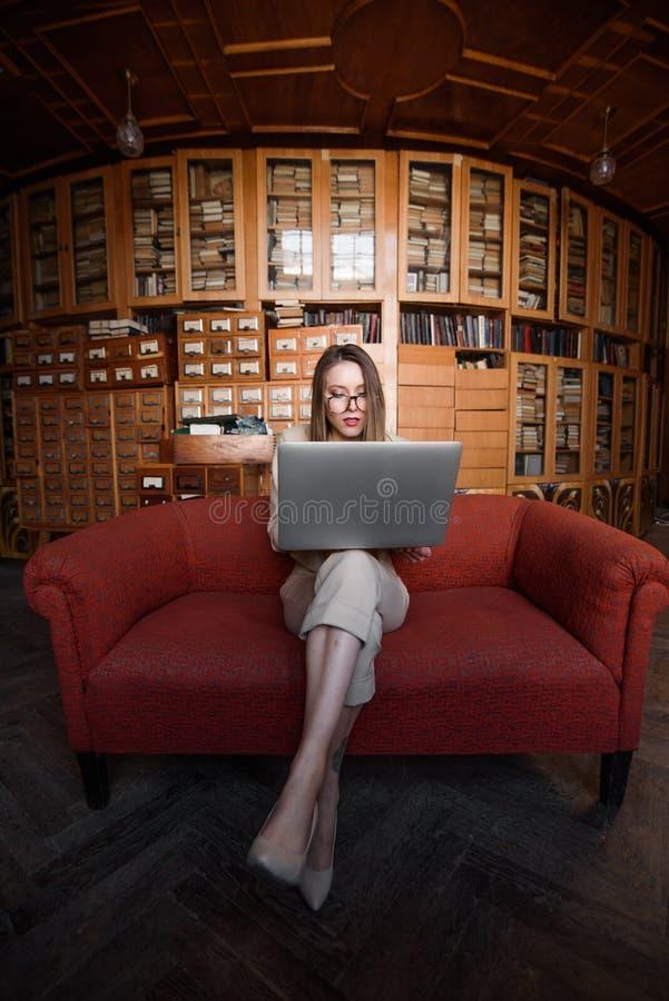 Дама дела сидит на красной софе и работает в ее компьтер-книжке стоковое изображение
