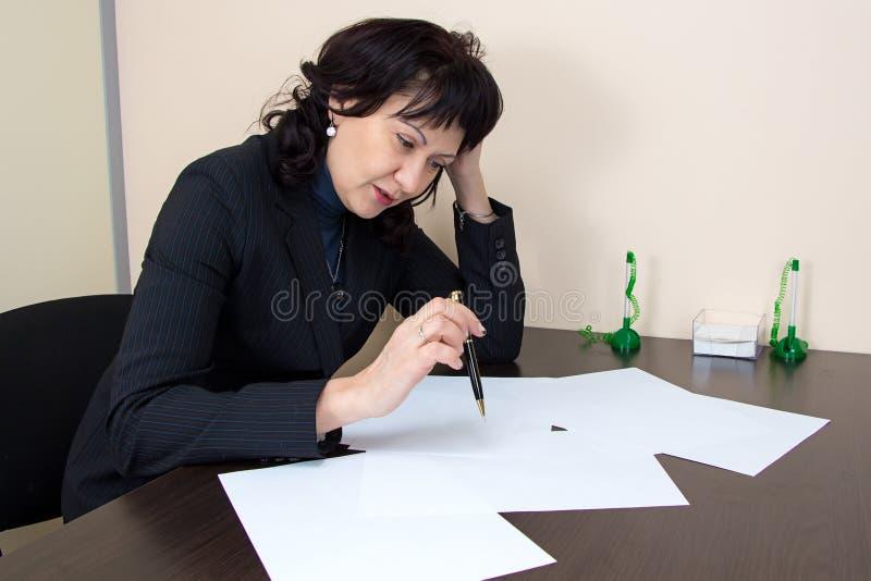 Дама дела сидя в офисе стоковое фото