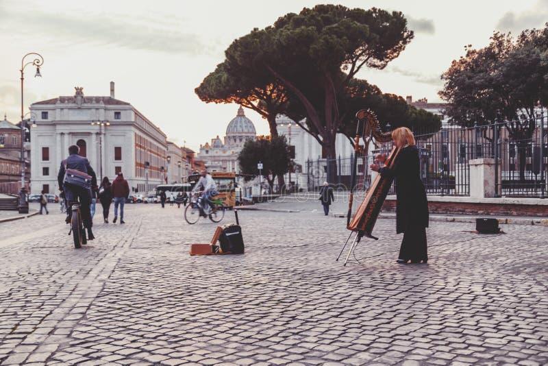Дама музыканта улицы играя арфу около Ватикана, Рима, Италии стоковая фотография