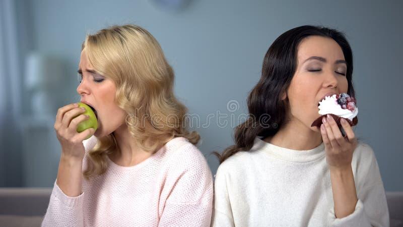 Дама наслаждаясь тортом, женским другом есть яблоко, индивидуальный выбор свойственной еды стоковое изображение rf