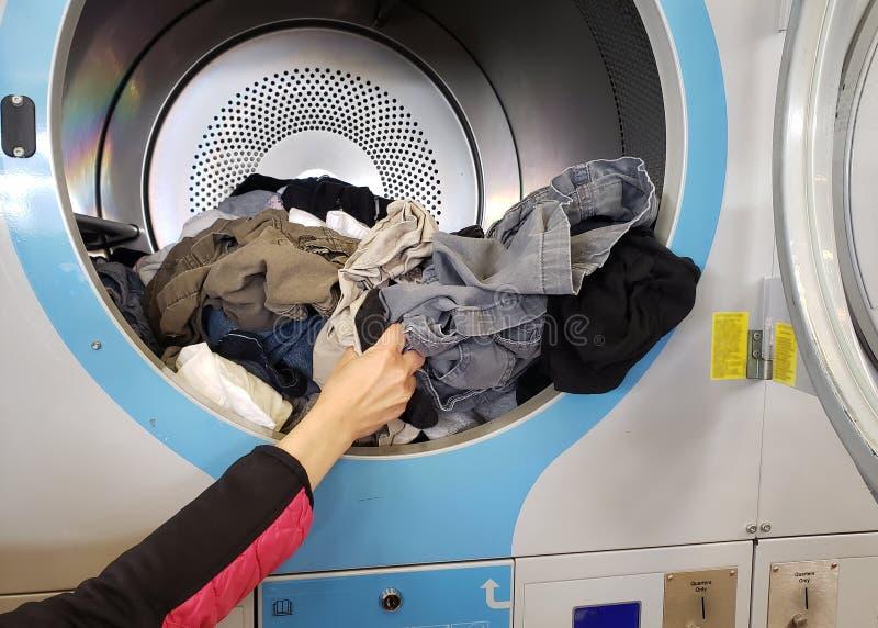 Дама принимает высушенную одежду вне от машины стоковое фото