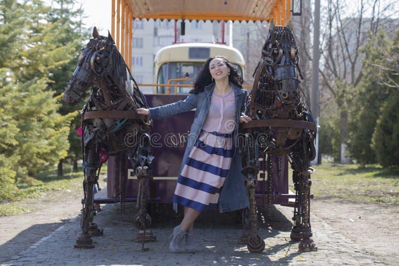 Дама стоя между 2 лошадями металла стоковые фотографии rf