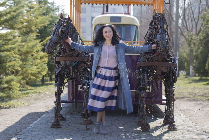 Дама стоя между 2 лошадями металла стоковые фото