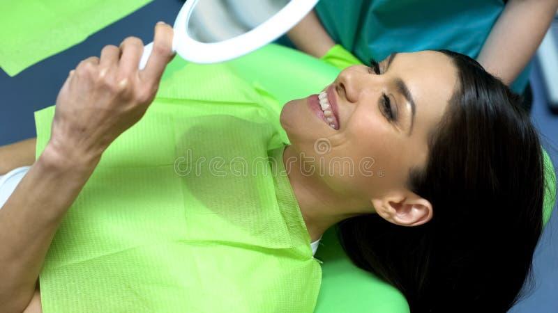 Дама счастливая с результатом зубоврачебной обработки, зубоврачевания профессиональной помощи косметического стоковое фото rf
