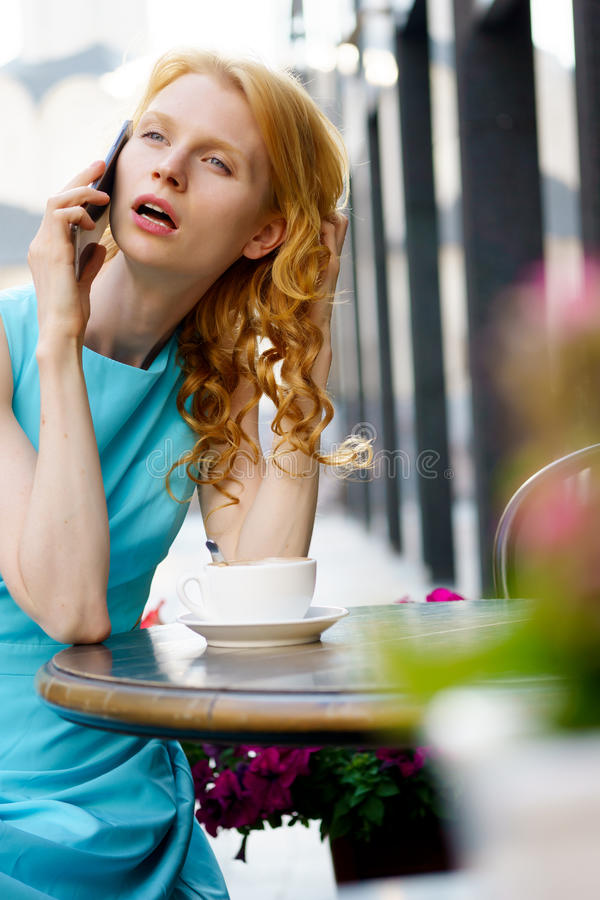 Дама с курчавыми белокурыми волосами говоря на телефоне в кафе стоковое изображение rf