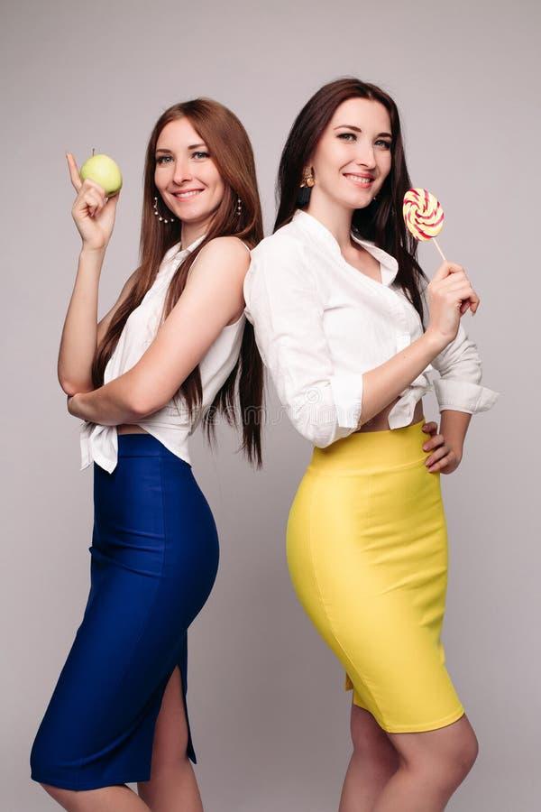 2 дамы красивых брюнета молодых с конфетой и яблоком стоковое изображение