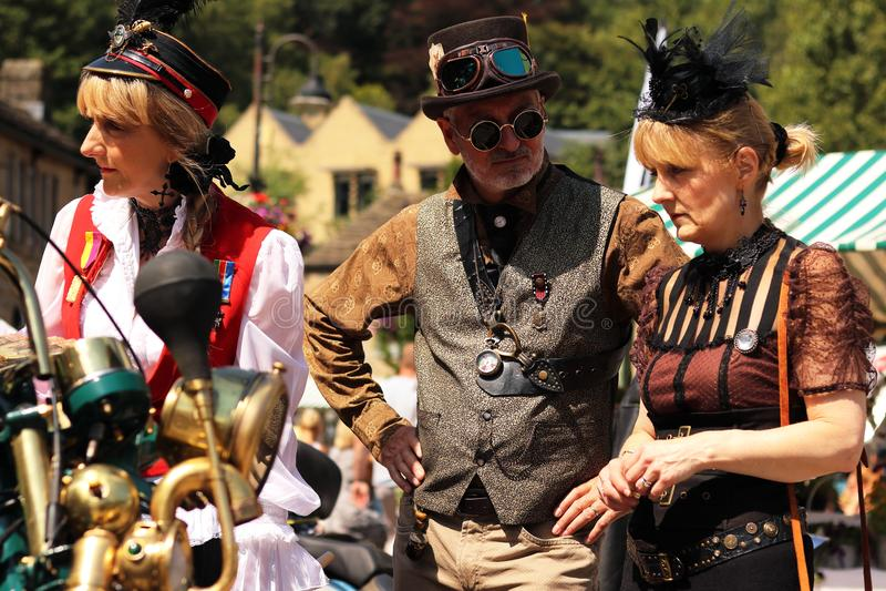 Дамы Steampunk моста Hebden красивые с шляпой Steampunk с изумлённым взглядом и человеком Steampunk стоковые фотографии rf