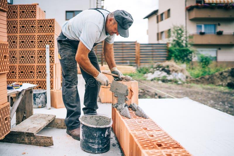 данные о промышленности - кирпичные стены экстерьера здания каменщика работника стоковые изображения rf