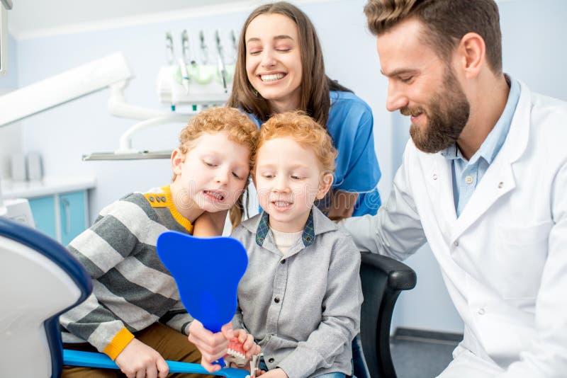 Дантисты с мальчиками на зубоврачебном officee стоковое фото