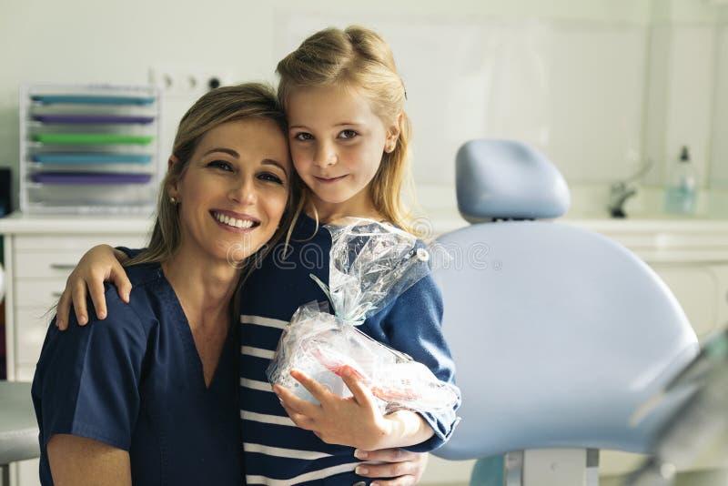 Дантисты с пациентом во время зубоврачебной интервенции к девушке стоковое фото