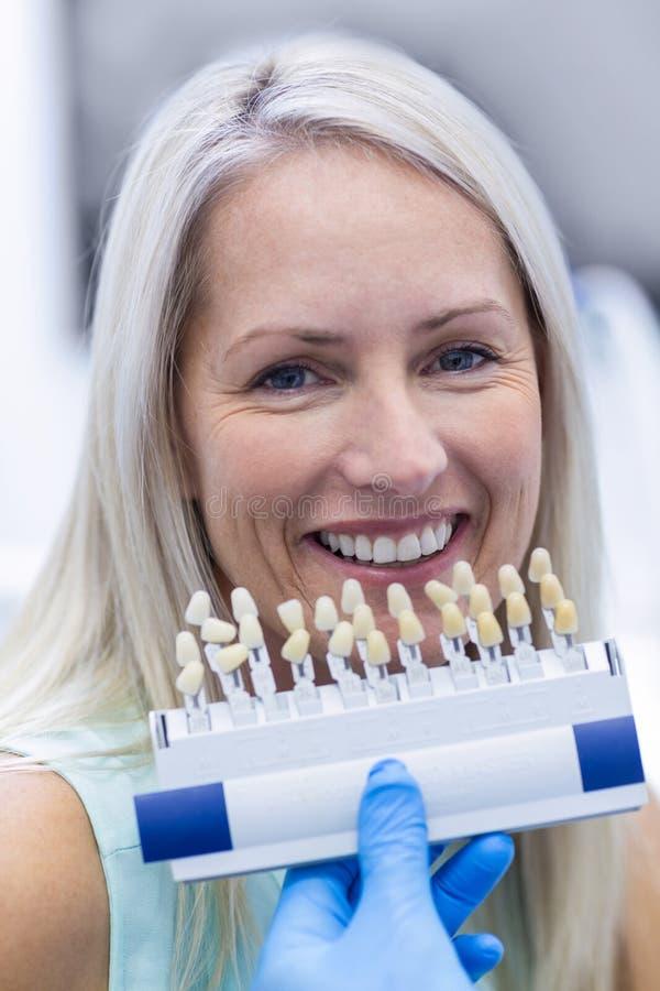 Дантист держа тени зубов пока женский терпеливый усмехаться стоковые изображения