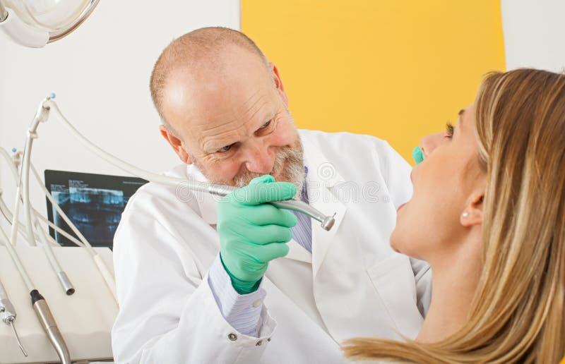 Дантист используя зубоврачебное сверло на женском пациенте стоковые изображения