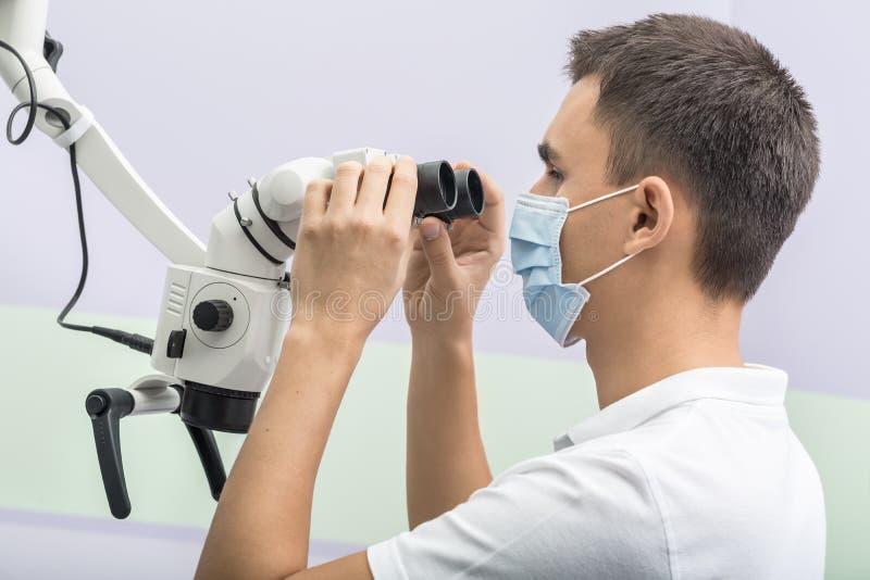 Дантист используя зубоврачебный микроскоп стоковое фото