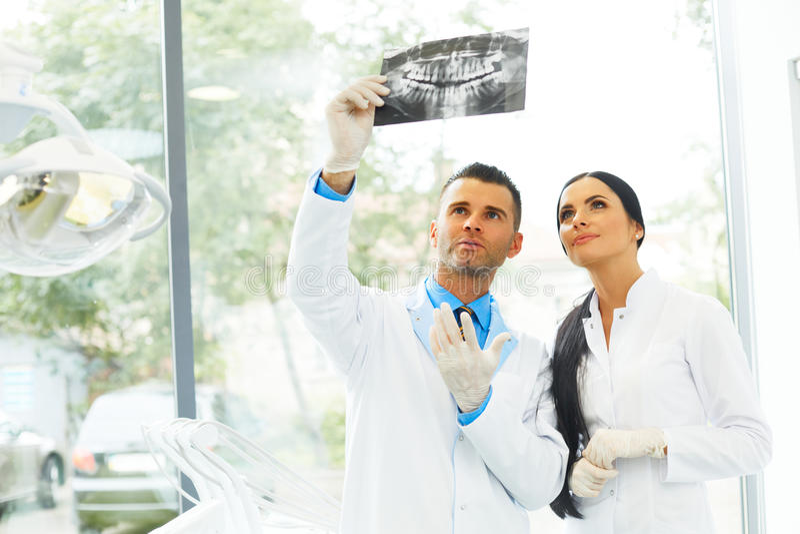 Дантист и женский ассистент обсуждают зубоврачебное изображение x Рэй стоковые фото