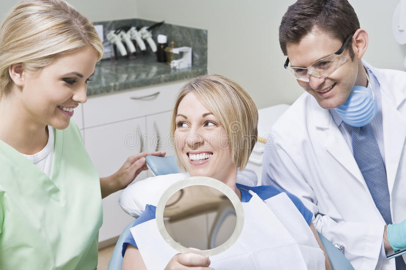 Дантист и пациент используя зеркало стоковое изображение