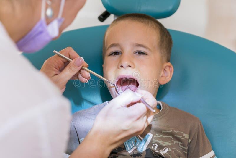 Дантист обрабатывает зубы ` s мальчика Зубоврачевание ` s детей, педиатрическое зубоврачевание Женское stomatologist обрабатывает стоковые изображения