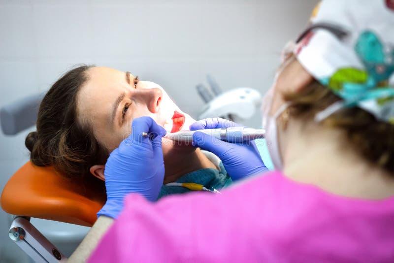 Дантист обрабатывает терпеливые зубы в зубоврачебной клинике стоковые изображения
