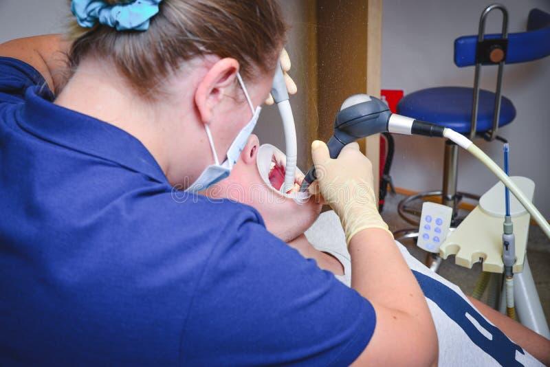 Дантист обрабатывая зубы к пациенту женщины в клинике Женское профессиональное stomatologist доктора на работе Зубоврачебное обор стоковые фото